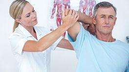 Physical therapist manipulation man's shoulder