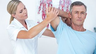 Physical therapist assisting a patient stretch their neck and upper back.