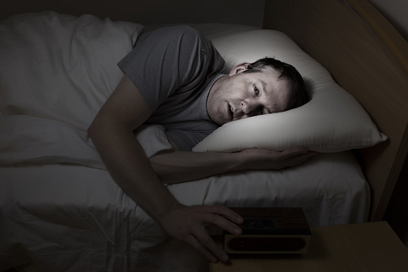 man dealing with insomnia in bed