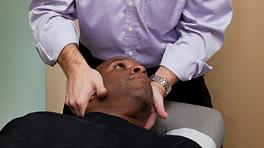 Chiropractor adjusting a supine patient's cervical spine.