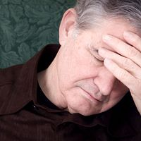 Senior man grabbing his head in pain.