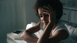 Woman sitting in bed, holding her forehead in pain.