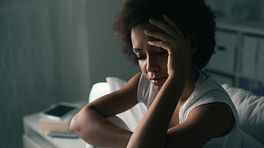 Woman sitting on bed suffering from insomnia and depression