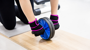 Image of hands using and ab roller in the gym