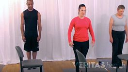 Three people doing a standing hamstring stretch.