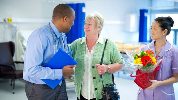 A woman talking with a doctor in a hospital setting