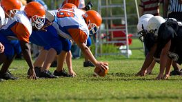 Two teams playing football at the line of scrimmage