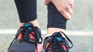 Runner grabbing their shin in pain.