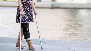 Woman walking on crutches.