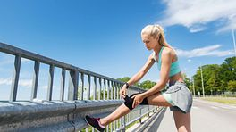 Woman adjusting her knee brace while out for a run.