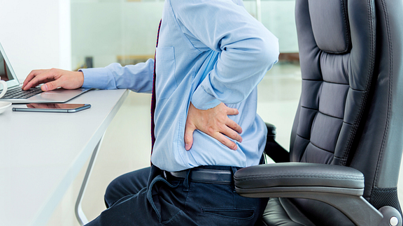 Image of a man seated at a desk grabbing his back in pain
