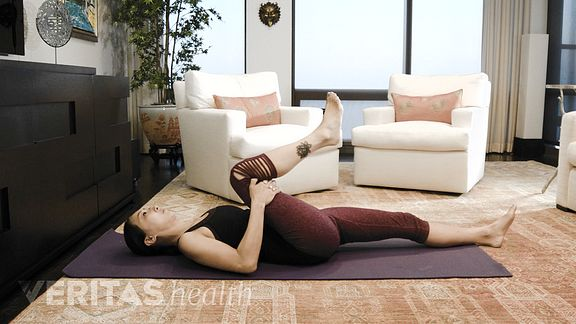 Woman performing the single knee-to-chest isometric stretch for sacroiliac joint pain