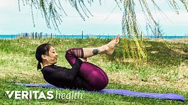Woman lying on the ground performing a back flexion stretch