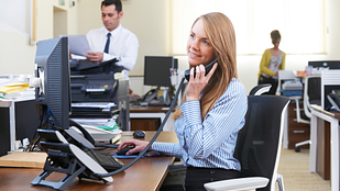 Image of a young professional women taking a phone call at her desk in a busy office.