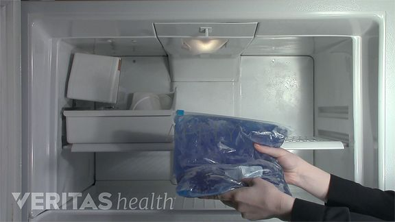Hands placing an icepack in the freezer