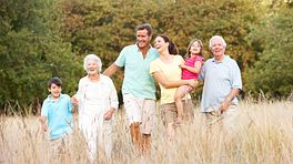 A multi generational family standing in a field