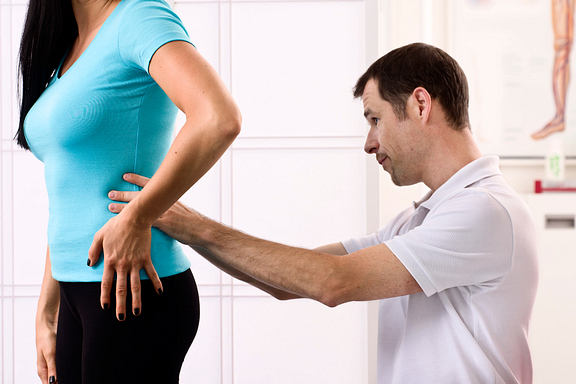 physical therapist examining patient's back