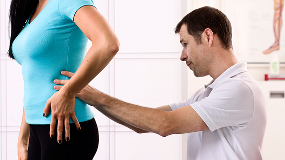 physical therapist examining patient's lower back