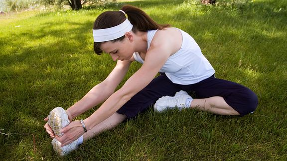Woman performing a seated hamstring stretch on the grass