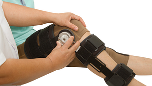 Physical therapist adjusting knee brace
