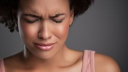 Woman wincing in pain from a headache.