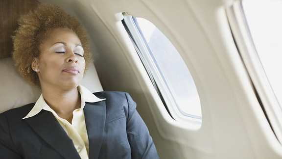 Image of woman napping in the window seat of an airplane