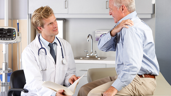 Image of an older man consulting a doctor about his shoulder pain