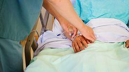 Nurse adjusting patient's intravenous tubing