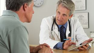 Image of a doctor and male patient discussing information on an iPad