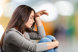 Image of girl sitting with her hand on her head in pain