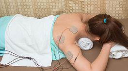 Woman lying prone with a TENS unit connected to the upper back.