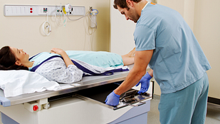 image of patient lying on X-ray table while X-ray technician switches out the X-ray films beneath her.