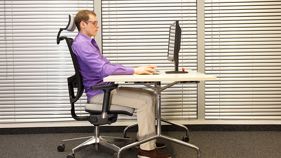 man sitting at ergonomic work station