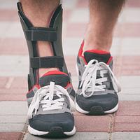 Feet walking in sneakers, one wearing an ankle orthotic brace.