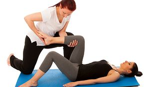 Therapist assisting patient with lower back stretches.