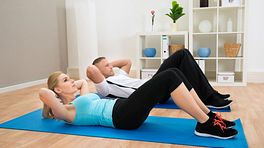 Two people performing sit-ups on yoga mats.