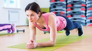 Young woman doing an exercise plank on green exercise mat