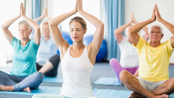 Yoga class doing the seated prayer pose