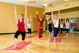 Yoga class doing warrior 1 yoga pose