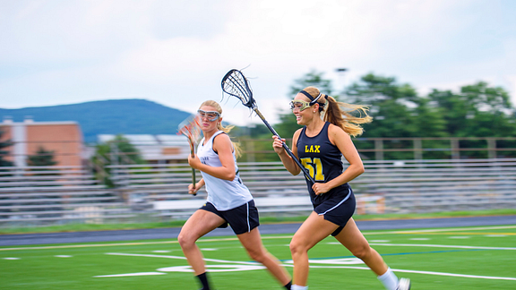 Two female lacrosse players running downfield