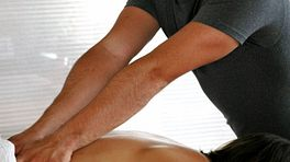 Massage therapist giving back massage on a patient lying prone