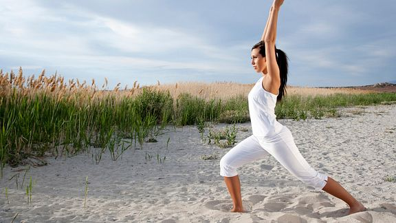 Woman performing yoga on the beach.