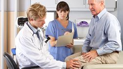 Doctor checking senior patient's knee