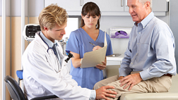 image of older man getting a knee examination in the exam room with his doctor and nurse