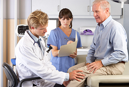 Older man getting his knee examined by a doctor
