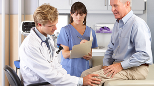 Older man getting a knee examination in the exam room with his doctor and nurse