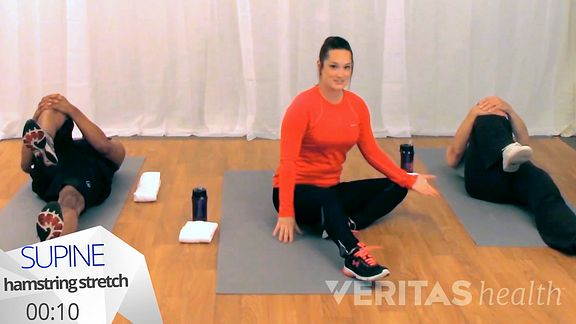 Woman sitting on the floor preparing to do the supine hamstring stretch