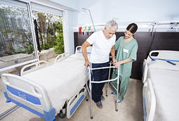 Image of a female caretaker helping a senior patient with walker in rehab center.