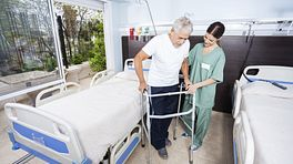 Man walking with a walker in a hospital for his recovery.