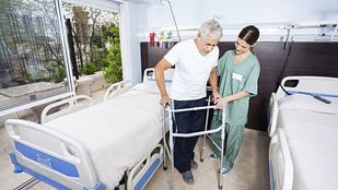 Image of an older man being assisted by a physician to use his walker in the hospital